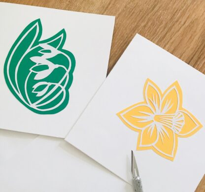 paper cut greetings cards.Snowdrop design with a green background on a white card and daffodil design with a yellow background on a white card