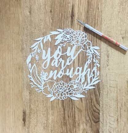 You are enough hand cut paper cut quote. Brush lettering style with a floral wreath border