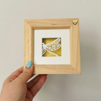 Miniature dragonfly paper cut. Hand cut from white paper and backed with shimmering golden paper in a wooden frame