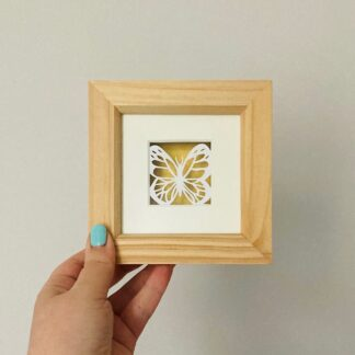 Miniature butterfly paper cut hand cut from white paper and backed on a shimmering gold in a wooden frame