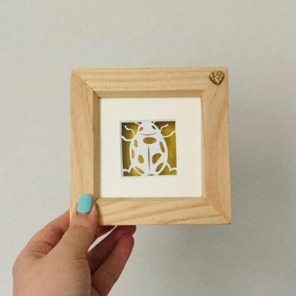 Miniature ladybird paper cut. Hand cut from white paper nad backed on shimmering gold paper in a wooden frame