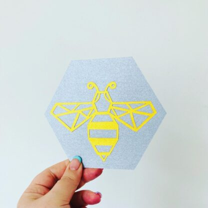 Bee paper cut in gold backed on a Grey hexagon by kppapercuts